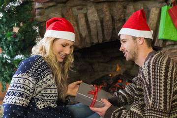 Man gifting woman in front of lit fireplace during Christmas