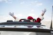 Leinwanddruck Bild - Santa With Arms Raised In Convertible Against Sky