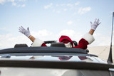 Santa With Arms Raised In Convertible Against Sky