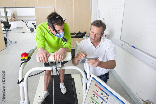Sports scientist and runner with mask on treadmill looking down at digital tablet in laboratory