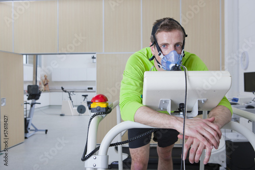 Portrait of runner with mask leaning on treadmill in sports science laboratory