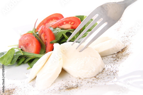 Caprese salad being eaten with a fork