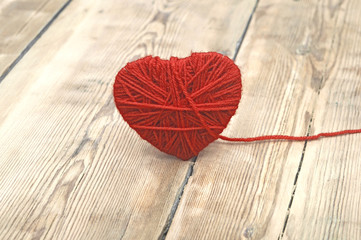 Heart made of red wool yarn on wood background