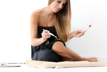 Woman sitting on the floor and painting