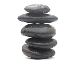 Black massage stones stacked, isolated on white
