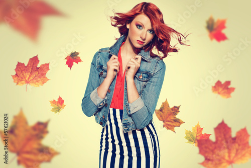 autumn picture of young beautiful red haired girl with leaves