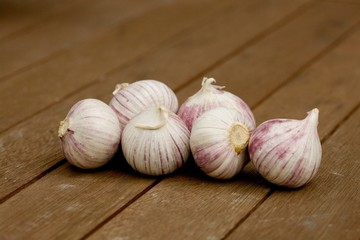 Few bulbs of garlic on wooden table