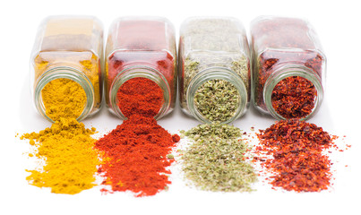 Different spices spilling from spice jars isolated on white