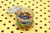 Colorful candies in glass jar on polka dot napkin