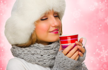 Young girl with mug on winter background