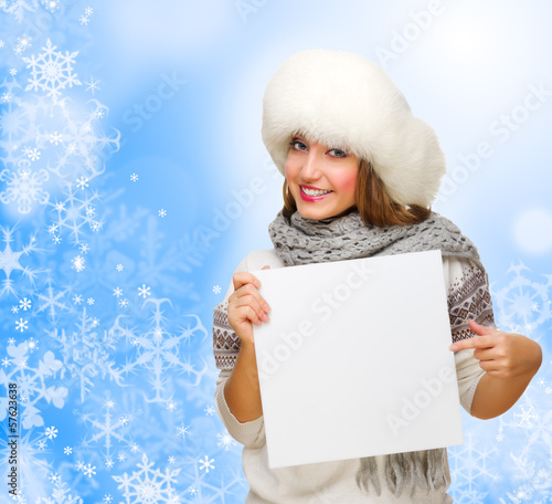 Young girl with empty card on winter background