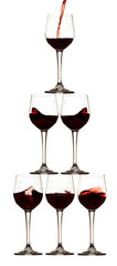 Piramide di bicchieri di vino rosso con bottiglia che versa