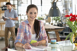 Portrait of smiling woman with cell phone and paperwork at kitchen table