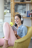 Smiling woman text messaging with cell phone and listening to music on headphones with digital tablet