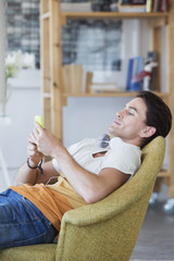 Man text messaging with cell phone in armchair