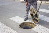 utilities worker moves the manhole cover 2