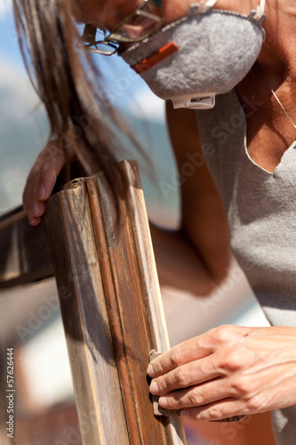 Do it yourself scene with a girl sanding a window