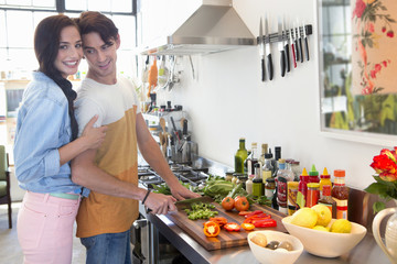 Portrait of smiling couple cooking in kitchen