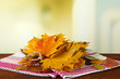 Beautiful autumn leaves on table on bright background