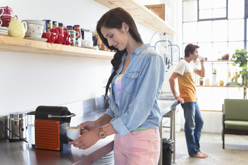 Smiling woman preparing espresso in kitchen