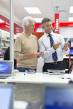 Salesman showing senior man digital tablet in electronics store
