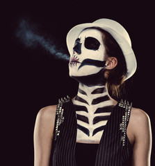 Woman with skeleton face art smoking, conceptual photo