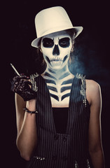 Woman with skeleton face art smoking over black background