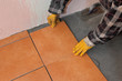 Home renovation, worker placing ceramic tile to cement at floor