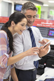 Salesman showing woman cell phone in electronics store