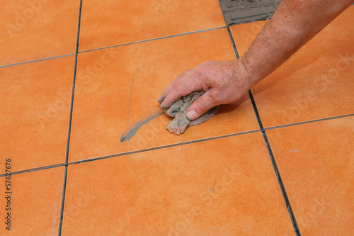 Home renovation, worker cleaning tile with rag