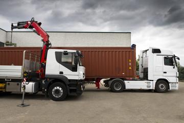 Camion con container che viene caricato da una gru. Due camion.
