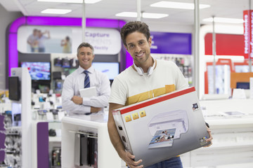 Portrait of smiling man holding printer box in electronics store
