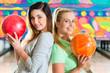 Junge Frauen spielen Bowling auf Bowlingbahn