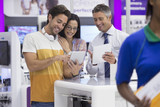 Salesman showing couple digital tablets in electronics store