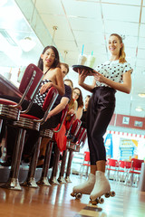 People in American diner or restaurant with waitress