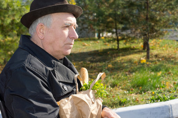 Elderly pensive man with a bag of groceries