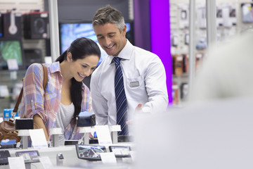 Smiling salesman showing woman digital cameras in electronics store