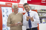 Salesman showing senior man cell phone in electronics store