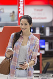Portrait of smiling woman looking at cell phones in electronics store