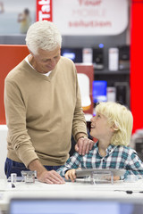 Grandfather and grandson looking at digital tablets in electronics store