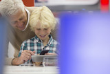 Smiling grandfather and grandson looking at cell phone and digital tablet in electronics store