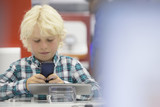 Boy looking at cell phone in electronics store