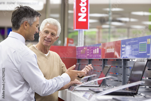 Salesman showing senior man laptops in electronics store