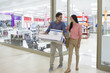 Smiling couple leaving electronics store with boxes