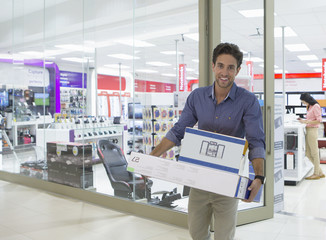 Portrait of smiling man leaving electronics store with boxes