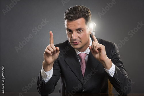 Think smart. Businessman holding glowing bulb at his temple