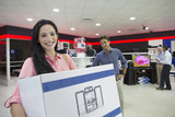 Portrait of smiling woman holding box in electronics store