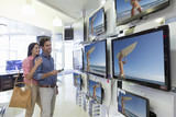 Smiling couple looking at surfer on flat screen televisions in electronics store