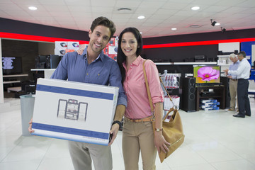 Portrait of smiling couple holding box in electronics store