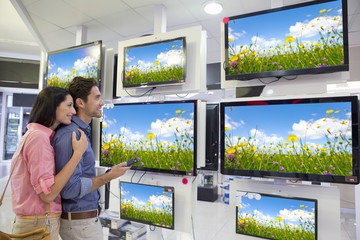 Smiling couple looking at wildflowers on flat screen televisions in electronics store